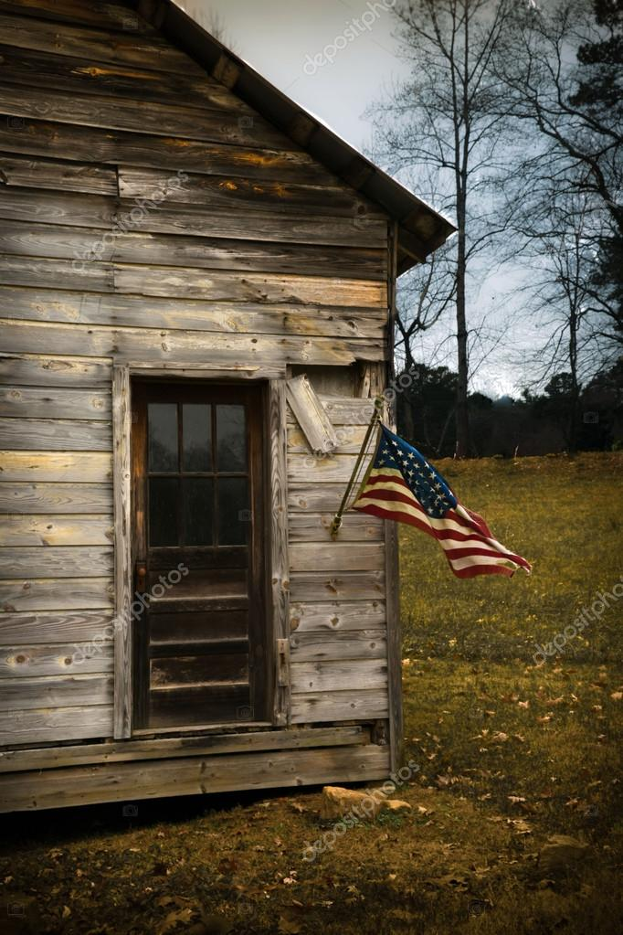 USA Flag Hangs From an Old Cabin