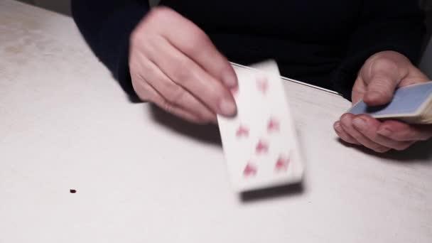 Ruce postarší ženy položily na stůl kartičky věštící budoucnost. Solitaire, věštění.