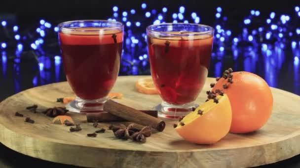 zwei Gläser Glühwein rotieren auf einem Holzteller auf schwarzem Hintergrund