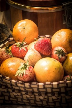 Fresh strawberries and oranges in basket