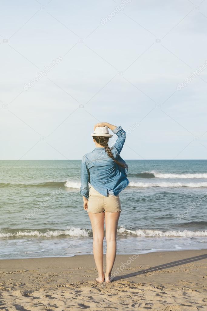 Woman walking away on the idylic beach.