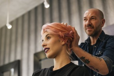 Beautiful woman getting haircut by hairdresser.