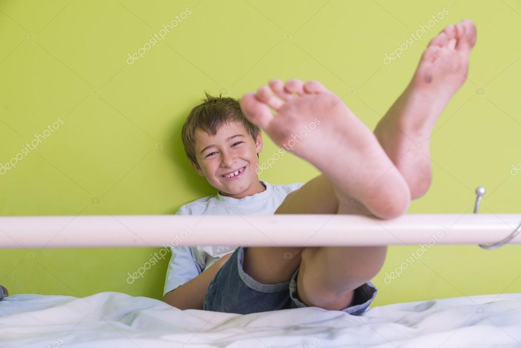 Little kid smiling with dirty feet and sitting at bed