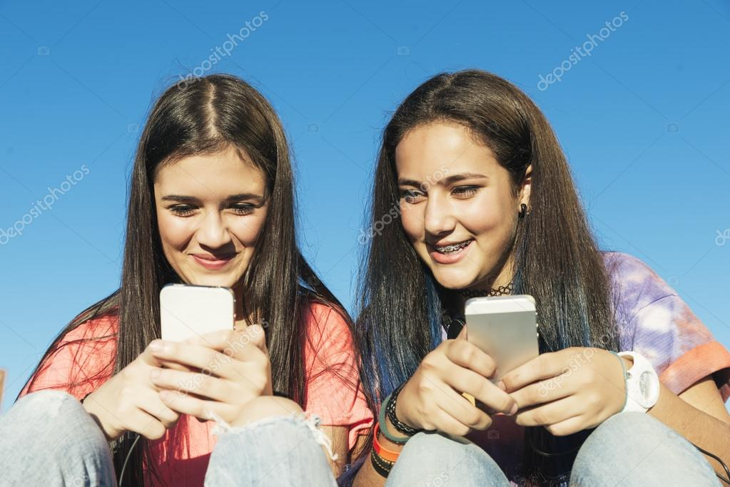 aedb4f9442f Duas adolescentes usando Mobile no parque — Stock Photo © santypan ...