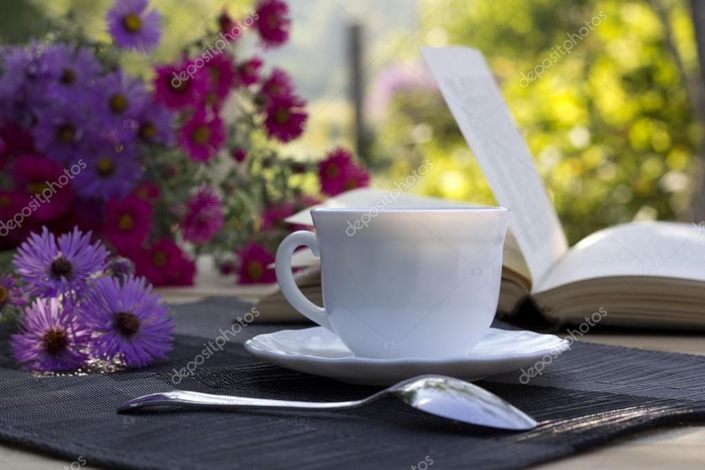 cup of tea , a bouquet of flowers and a book