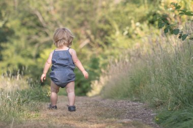 Baby girl walks away on green forest path