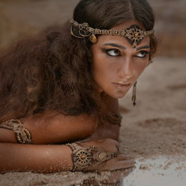 Beautiful girl in ethnic jewelry and mirror covered with sand