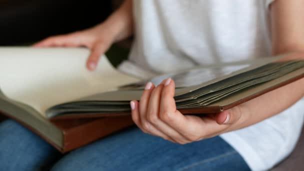 Žena se dívá na černobílé fotografie na stránkách rodinného fotoalba. Osoba obrací stránky starého fotoalba