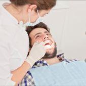 mladý šťastný muž a žena v zubní prohlídce u zubaře