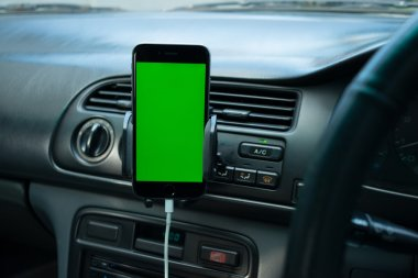 Smartphone with green screen on generic car's dashboard