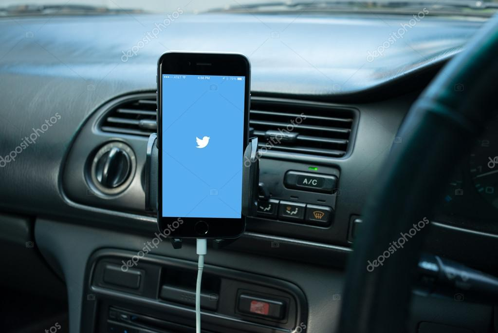 Smartphone mounted on a generic car's dashboard with social media on its screen.