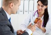 schöne Medizinerin gibt männlichen Patienten Pillen