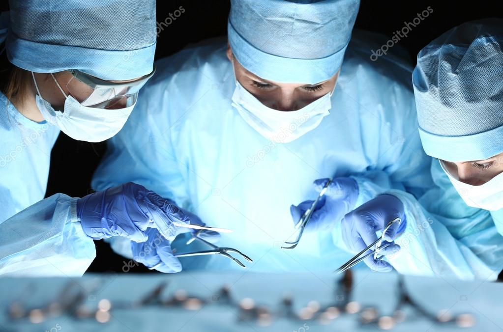Group of surgeons at work operating in surgical theatre
