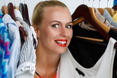 Beautiful smiling blonde woman standing inside wardrobe rack ful