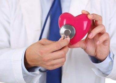 Male medicine doctor holding red heart