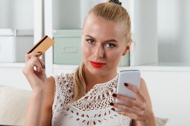 Beautiful blonde woman holding golden credit