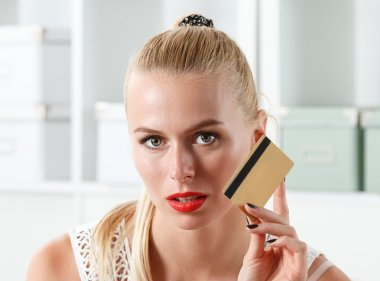 Beautiful blonde woman holding golden credit card