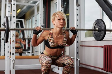 Reliefed athlete blonde woman making squats in power rack