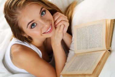 Young beautiful smiling blonde woman lying in bed reading book
