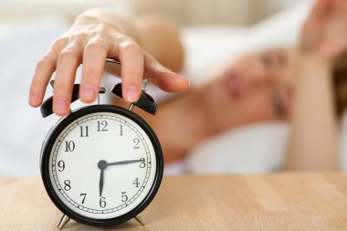 Stretching hand of sleepy young woman trying kill alarm clock