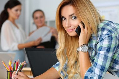 Beautiful blond female designer in office talking cellphone