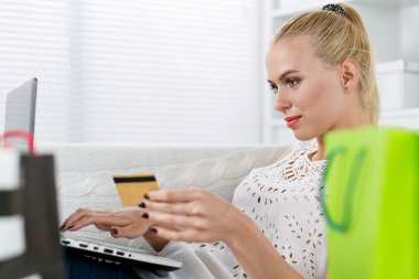 Beautiful blonde woman making shopping via internet looking in n