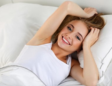 Young beautiful blonde smiling woman portrait wake up early morn