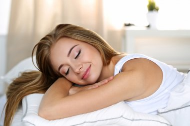 Young beautiful blonde woman portrait lying in bed