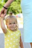 Lustiges kleine Mädchen im freien halten Mütter Hand Portrait lächelnd