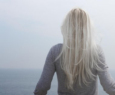 Blond girl standing against the sea from her back