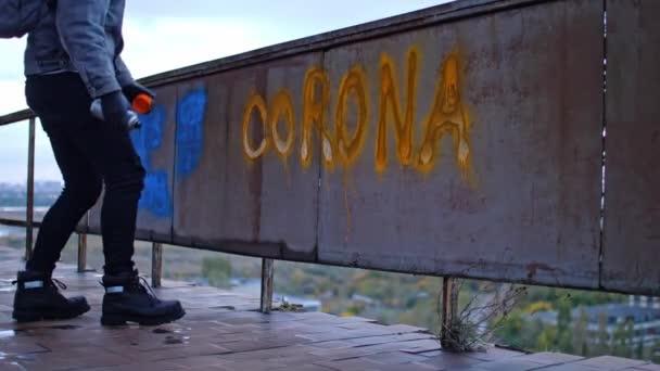 Mladý protestant v džínové bundě jde ven po výrobě graffiti corona