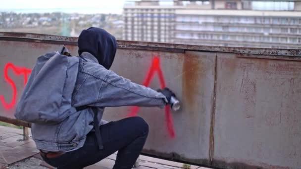 Proces tvorby anarchie graffiti mladým protestantem v kapuci