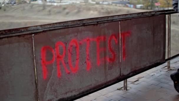 Protester jde ven po protestní graffiti s červeným sprejem barvy