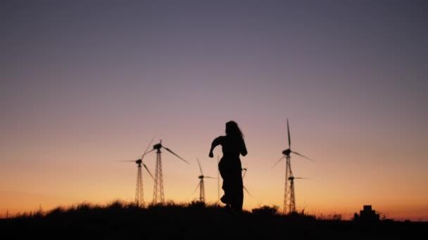 Slow-motion scene of pretty girls silhouette runs trough the hills near windmill