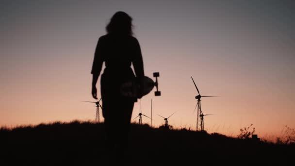 Silhouette auf Windkraftanlagen im Sonnenuntergang in der Nähe eines hübschen Mädchens mit Skateboard