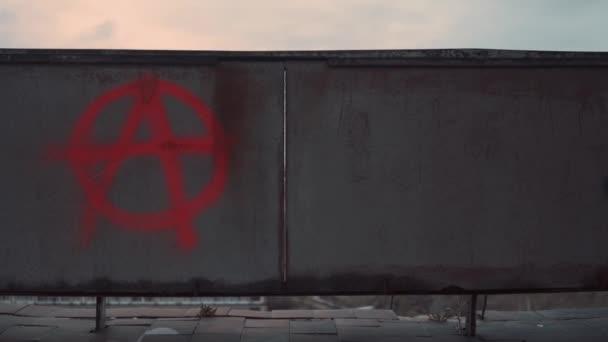 Symbol anarchie namalovaný červeným sprejem na staré opuštěné zdi