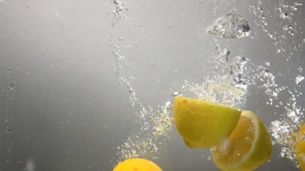 Části citronu klesne pod vodou. Šedé pozadí