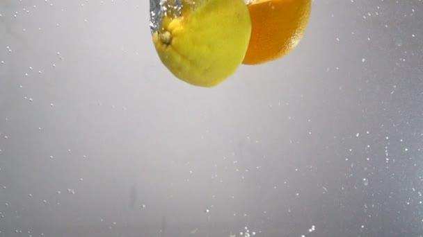 Zitrone und Orange fallen in Zeitlupe ins Wasser