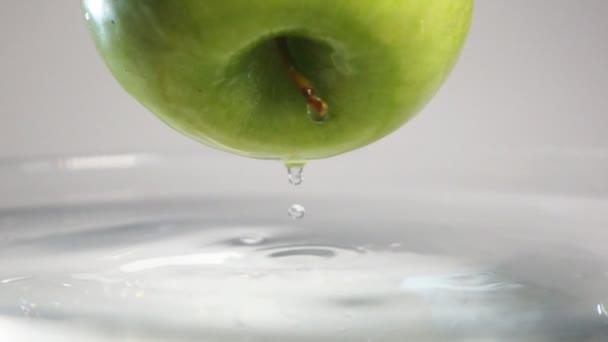Kapky vody padají od apple do vody