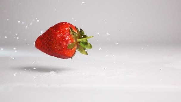 Strawberries fall on white wet surface
