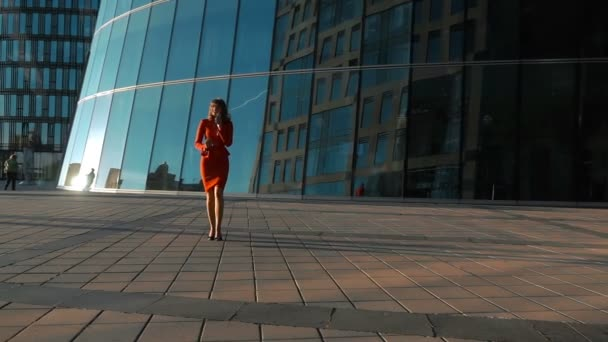 Businesswoman in red suit using smart phone