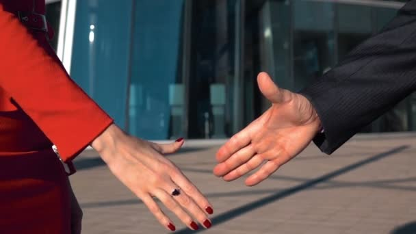 Podnikatel a podnikatelka si potřásají rukama