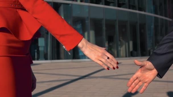 Business partners men and women doing a handshake