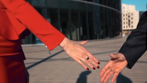 Obchodní partneři mužů a žen dělá handshake