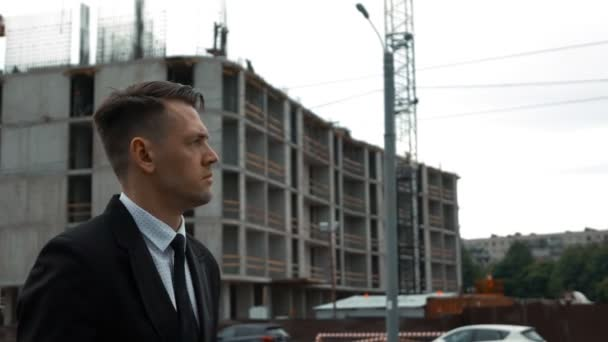 Businessman in suit walking near newly constructed building