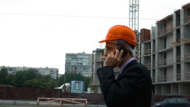 Builder in helmet talking on a smart phone.