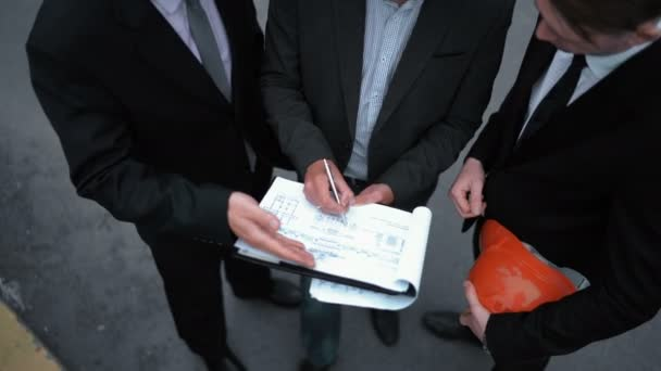 Business people signing architecture documents