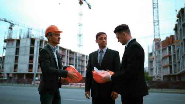 Engineer giving businessmen helmets