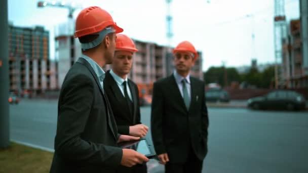 Bauarbeiter und Geschäftsleute im Gespräch vor Ort