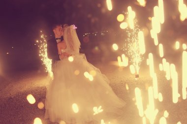 Bridal couple dancing sorrounded by fireworks